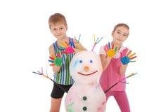 Το όμορφα αγόρι και το κορίτσι με παραδίδουν το χρώμα κοντά στο χιονάνθρωπο χρώματος με τα χρωματισμένα κέρατα και τα χέρια Στοκ Εικόνες