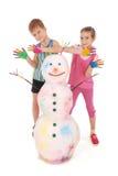 Το όμορφα αγόρι και το κορίτσι με παραδίδουν το χρώμα κοντά στο χιονάνθρωπο χρώματος με τα χρωματισμένα κέρατα και τα χέρια Στοκ Φωτογραφία