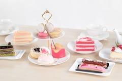 Το όμορφα κέικ και το επιδόρπιο στον ξύλινο πίνακα στην κρητιδογραφία χρωματίζουν - μαλακή εστίαση στοκ φωτογραφίες