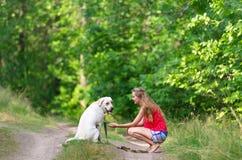 Το όμορφα κορίτσι και το σκυλί έχουν καθίσει σε ένα δασικό μονοπάτι Στοκ φωτογραφία με δικαίωμα ελεύθερης χρήσης