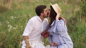 Το όμορφες άτομο και η έγκυος γυναίκα ζευγών τρώνε τα κόκκινα σταφύλια τρόφιμα υγιή νωποί καρποί Ευτυχές χαμόγελο γυναικών φιλμ μικρού μήκους