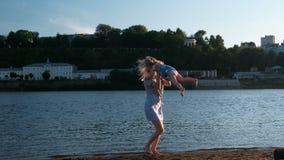 Το όμορφες ξανθές mom και η κόρη τρέχουν το ένα προς το άλλο στην όχθη ποταμού στο ηλιοβασίλεμα απόθεμα βίντεο