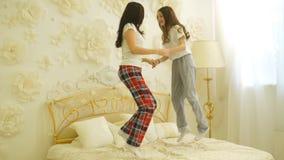 Το όμορφες mom και η κόρη έχουν τη διασκέδαση πηδώντας στο κρεβάτι στο σπίτι φιλμ μικρού μήκους