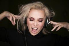 Το όμορφο άκουσμα γυναικών τη μουσική μέσω των ακουστικών και τραγουδά στοκ εικόνες