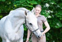 Το όμορφο άσπρο άλογο μεταχειρίζεται από το νέο χέρι έφηβη ` s στοκ εικόνα με δικαίωμα ελεύθερης χρήσης