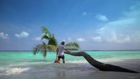 Το όμορφο άτομο απολαμβάνει διακοπές σε μια εγκαταλειμμένη τροπική παραλία απόθεμα βίντεο