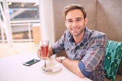 Το όμορφο άτομο εξετάζει ευθύ τη συνεδρίαση καμερών στον καφέ Στοκ Φωτογραφίες