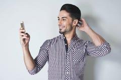 Το όμορφο άτομο εξετάζει το τηλέφωνο κυττάρων του Στοκ φωτογραφία με δικαίωμα ελεύθερης χρήσης