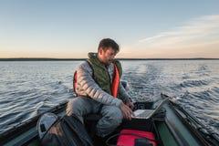 Το όμορφο άτομο κάθεται στη βάρκα και εργάζεται με το lap-top Στοκ Εικόνα