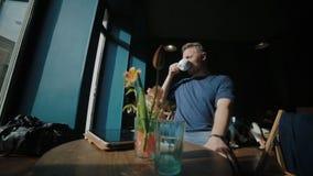 Το όμορφο άτομο κάθεται στον καφέ και έχει ένα υπόλοιπο απόθεμα βίντεο