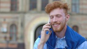 Το όμορφο άτομο με τη σγουρές τρίχα και τη γενειάδα πιπεροριζών μιλά ευτυχώς μέσω του κινητού τηλεφώνου περπατώντας κατά μήκος τη απόθεμα βίντεο