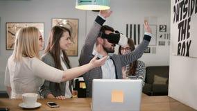 Το όμορφο άτομο δοκιμάζει app για τα γυαλιά εικονικής πραγματικότητας κρανών VR οι φίλοι και οι συνάδελφοί του που υποστηρίζουν τ Στοκ Φωτογραφία