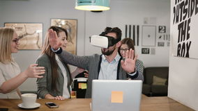 Το όμορφο άτομο δοκιμάζει app για τα γυαλιά εικονικής πραγματικότητας κρανών VR οι φίλοι και οι συνάδελφοί του που υποστηρίζουν τ Στοκ Φωτογραφίες