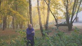 Το όμορφο άτομο που αισθάνεται τα κρύα και θερμαίνοντας χέρια, άτομο παγώνει στο πάρκο φθινοπώρου ψυχρά απόθεμα βίντεο