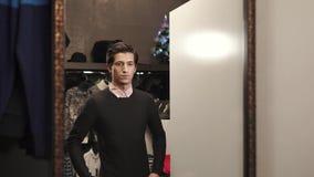 Το όμορφο άτομο προσπαθεί σε ένα μαύρο μαλακό πουλόβερ σε μια αίθουσα εκθέσεως του καταστήματος σχεδιαστών απόθεμα βίντεο