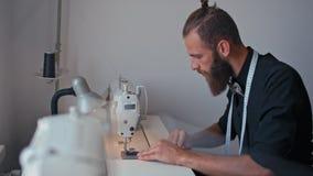 Το όμορφο άτομο ραφτών ράβει στη μηχανή κάνοντας τα ενδύματα στο στούντιο σχεδίου απόθεμα βίντεο