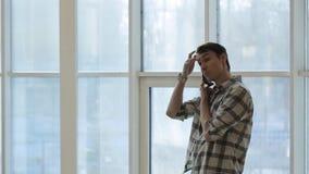 Το όμορφο άτομο στέκεται κοντά στο παράθυρο και μιλά στο smartphone απόθεμα βίντεο