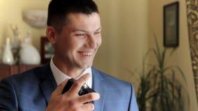 Το όμορφο άτομο στο διαμέρισμα χρησιμοποιεί την Κολωνία ευτυχής εκλεκτής ποιότητας γάμος ημέρας ζευγών ιματισμού απόθεμα βίντεο