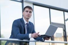 Το όμορφο άτομο στο κοστούμι στέκεται κοντά στο γραφείο και το χαμόγελό του Στοκ Φωτογραφίες