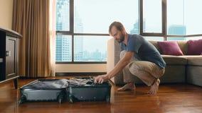 Το όμορφο άτομο συσκευάζει μια βαλίτσα σε ένα δωμάτιο με ένα πανοραμικό παράθυρο αγνοώντας τους ουρανοξύστες στοκ εικόνες με δικαίωμα ελεύθερης χρήσης