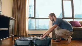 Το όμορφο άτομο συσκευάζει μια βαλίτσα σε ένα δωμάτιο με ένα πανοραμικό παράθυρο αγνοώντας τους ουρανοξύστες στοκ φωτογραφία με δικαίωμα ελεύθερης χρήσης