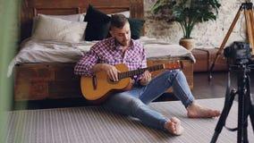 Το όμορφο άτομο blogger και ο κιθαρίστας καταγράφουν το τηλεοπτικό μάθημα για την κιθάρα χρησιμοποιώντας τη κάμερα Ο γενειοφόρος  απόθεμα βίντεο