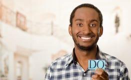 Το όμορφο άτομο Headshot που κρατά ψηλά τα μικρά γράμματα που συλλαβίζουν τη λέξη κάνει και που χαμογελούν στη κάμερα Στοκ Εικόνες