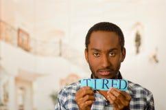 Το όμορφο άτομο Headshot που κρατά ψηλά τα μικρά γράμματα που συλλαβίζουν τη λέξη κούρασε και που κοιτάζουν στη κάμερα Στοκ φωτογραφίες με δικαίωμα ελεύθερης χρήσης