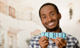 Το όμορφο άτομο Headshot που κρατά ψηλά τα μικρά γράμματα που συλλαβίζουν τη λέξη κούρασε και που χαμογελούν στη κάμερα Στοκ εικόνα με δικαίωμα ελεύθερης χρήσης