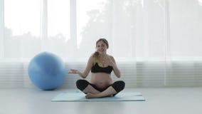 Το όμορφο έγκυο κορίτσι με μια μεγάλη κοιλιά χορεύει στη συνεδρίαση δωματίων ικανότητας στο πάτωμα στη θέση λωτού απόθεμα βίντεο