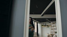 Το όμορφο έγκυο κορίτσι στο πράσινο φόρεμα βραδιού κοιτάζει στον καθρέφτη φιλμ μικρού μήκους