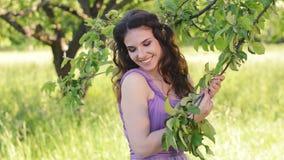 το όμορφο έξυπνο κορίτσι αποτελεί το πορτρέτο Καυκάσια γυναίκα brunette που θέτει και που εξετάζει τη κάμερα στην πασχαλιά ή απόθεμα βίντεο
