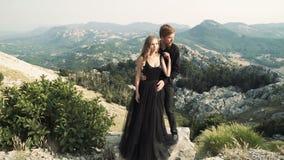 Το όμορφο αγάπης πρότυπο γυναικών ζευγών νέο σε ένα έξυπνο μακρύ φόρεμα και ένας άνδρας στο Μαύρο ταιριάζουν την τοποθέτηση στη κ απόθεμα βίντεο