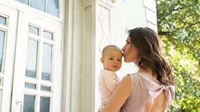 Το όμορφο αγκάλιασμα mum και δίνει τα φιλιά στο εύθυμο νήπιο στην πίσω αυλή απόθεμα βίντεο