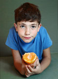 Το όμορφο αγόρι τρώει το πορτοκαλί στενό επάνω πορτρέτο Στοκ Εικόνες