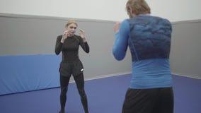 Το όμορφο αθλητικό κορίτσι διευθύνει ένα workout με έναν τύπο Να πυγμαχήσει τον τύπο και τα κορίτσια στη γυμναστική Εκπαιδευτικοί απόθεμα βίντεο