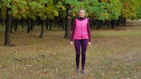 Το όμορφο αθλητικό κορίτσι ικανότητας θερμαίνει πρίν τρέχει στο πάρκο φθινοπώρου Workout υπαίθρια φιλμ μικρού μήκους