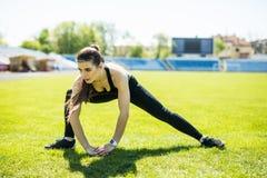 Το όμορφο αθλητικό κορίτσι συμμετέχει σε ένα αθλητικό στάδιο Ζέσταμα των μυών πρίν εκπαιδεύει στοκ εικόνα