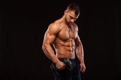 Το όμορφο αθλητικό άτομο δύναμης με τον αλτήρα κοιτάζει με βεβαιότητα προς τα εμπρός Το ισχυρό bodybuilder με έξι συσκευάζει, τελ στοκ εικόνες με δικαίωμα ελεύθερης χρήσης
