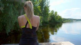 Το όμορφο, αθλητικό νέο ξανθό τέντωμα γυναικών, κάνοντας τις διαφορετικές ασκήσεις, άλμα, lunges, κάθεται οκλαδόν Λίμνη, ποταμός, φιλμ μικρού μήκους