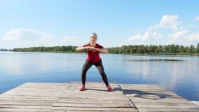 Το όμορφο, αθλητικό νέο ξανθό τέντωμα γυναικών, κάνοντας τις διαφορετικές ασκήσεις, άλμα, lunges, κάθεται οκλαδόν Λίμνη, ποταμός, απόθεμα βίντεο