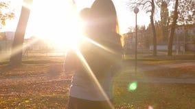 Το όμορφο ανεξάρτητο κορίτσι με μακρυμάλλη φέρνει τα χέρια λίγου μωρού στον περίπατο στο πάρκο κάτω από το έντονο φως της ρύθμιση απόθεμα βίντεο