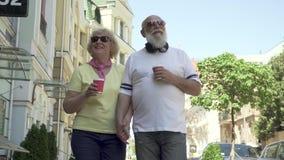 Το όμορφο ανώτερο ζεύγος πορτρέτου που περπατά στην πόλη και απολαμβάνει το ένα το άλλο φιλμ μικρού μήκους