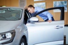 Το όμορφο αρσενικό επιλέγει ένα νέο αυτοκίνητο Έννοια επιτυχίας και τρόπου ζωής Στοκ Εικόνες