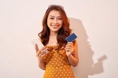 Το όμορφο ασιατικό θηλυκό κομψότητας απολαμβάνει on-line με την έννοια επιχειρησιακών ιδεών πιστωτικών καρτών και smartphone στοκ φωτογραφίες