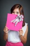 Το όμορφο ασιατικό κορίτσι κρατά ότι ένα κιβώτιο δώρων κλείνει το χαμηλότερο πρόσωπό της στοκ φωτογραφία