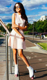 Το όμορφο ασιατικό κορίτσι με σκοτεινό μακρυμάλλη σε μια θερινά εξάρτηση και τα γυαλιά ηλίου που θέτουν στον κύλινδρο κάνει πατιν Στοκ Εικόνες