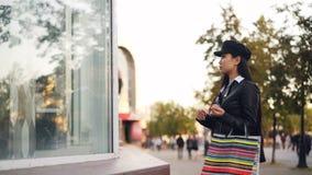 Το όμορφο ασιατικό κορίτσι στο μοντέρνο σακάκι δέρματος ιματισμού και την ΚΑΠ εξετάζει τη νέα συλλογή ενδυμάτων στις αγορές απόθεμα βίντεο