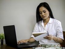 Το όμορφο ασιατικό freelancer που φαίνεται βιβλίο σημειώσεων, που δακτυλογραφεί στο πληκτρολόγιο labtop συγκεντρώνει την εργασία  στοκ φωτογραφία με δικαίωμα ελεύθερης χρήσης