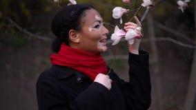 Το όμορφο αφρικανικό κορίτσι με το vitiligo που στέκεται sniffs οδών αναπηδά τα λουλούδια Άνθος άνοιξη Magnolia φιλμ μικρού μήκους